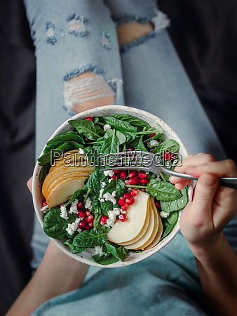 girl holding salad with spinach pear