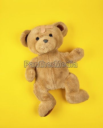 brown teddy bear on a yellow