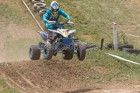 quad rider in blue jumping in