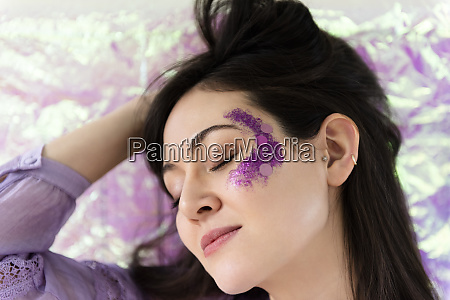 woman with purple glitter on cheek