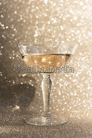 glass of champagne against glitter background