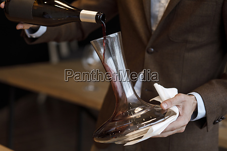 waiter pouring red wine into decanter