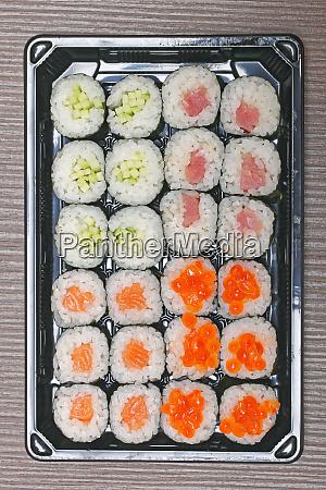 two dozen sushi rolls at tray
