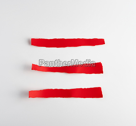 torn strips of red paper on