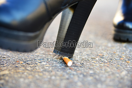 shoe pushes cigarette out with the
