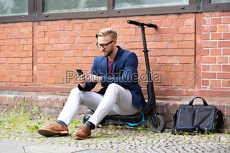 businessman sitting on electric scooter using