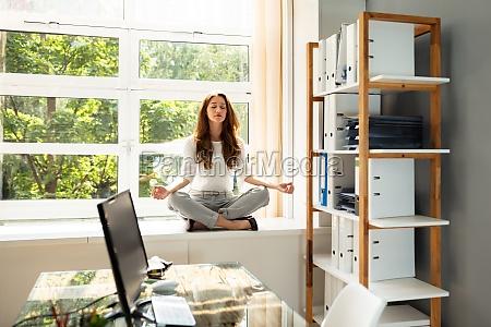 businesswoman meditating in lotus position