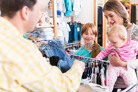 family looking at clothes on rail