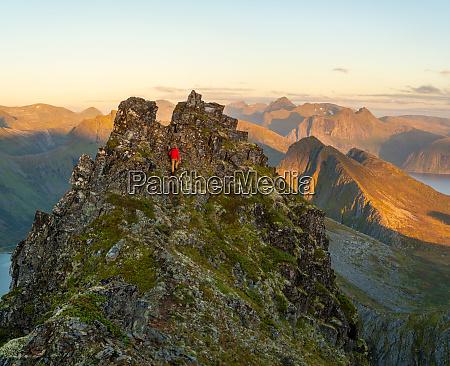 man climbing up a steep peak