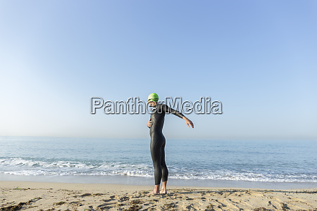 triathlete warming up before swimming in