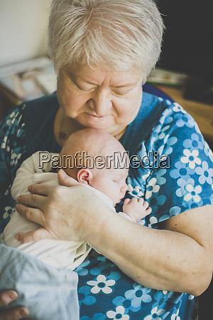 grandmother holding her sleeping baby granddaughter