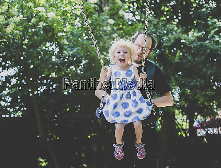 father pulling swing with girl at