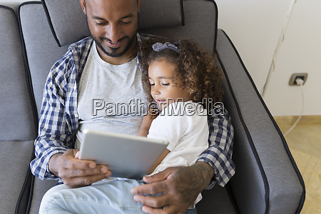 father and daughter sitting on couch