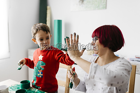 happy mother and son high fiving