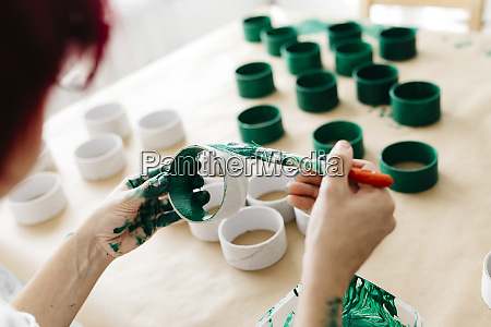 womans hands painting a roll of