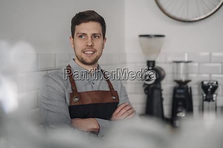 barista wearing apron standing in coffee