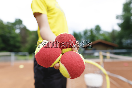 boy on the tennis court holding