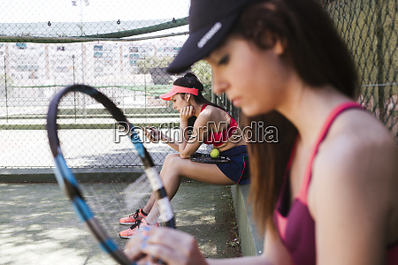 female tennis players sitting on court