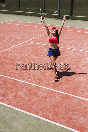 happy female tennis player cheering on