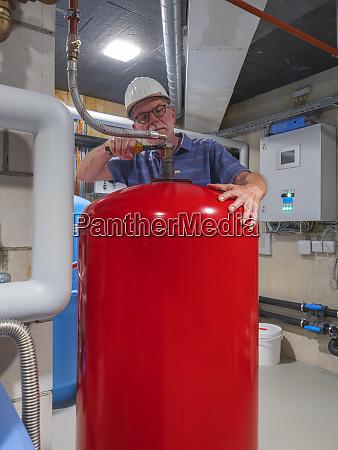 senior craftsman checking water processing unit