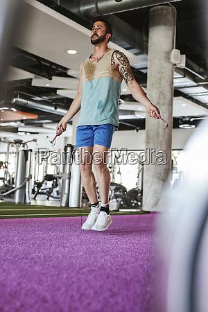 kickboxer training in fitness studio skipping