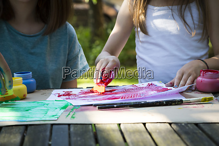 two girls painting at table in