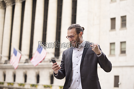 excited young businessman looking at cell