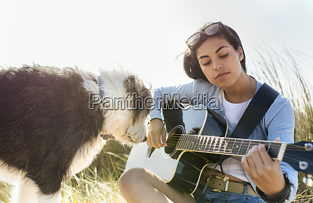 young woman with dog playing guitar