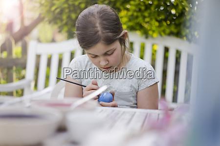 girl painting easter egg on garden