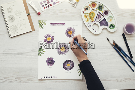 woman painting flowers with water colors