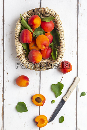 apricots in basket knife on white