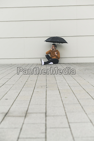 young man with umbrella sitting on