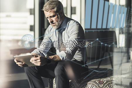 mature businessman using tablet surrounded by