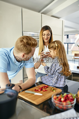 happy family eating fresh strawberries in