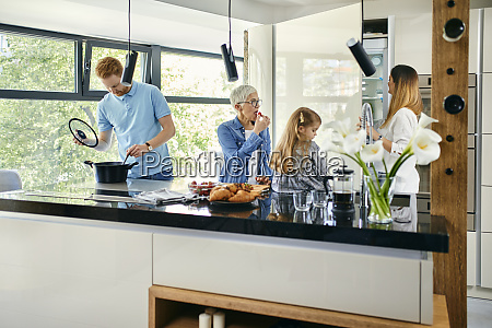 three genaration family preparing food in