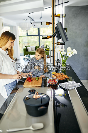 mother and daughter chopping strawberries in