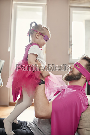 father and daughter playing superhero and