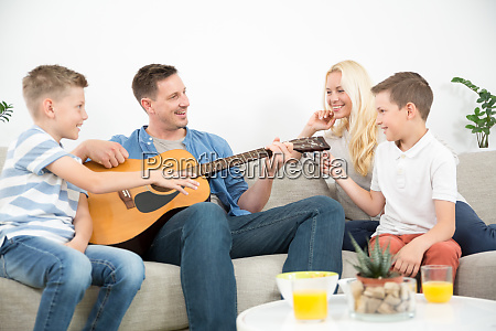 happy caucasian family smiling playing guitar