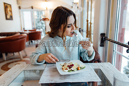 woman eating tasty vegetable salad in