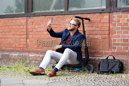 man sitting on electric scooter taking