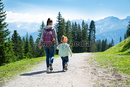 mother and daughter walking hiking trail