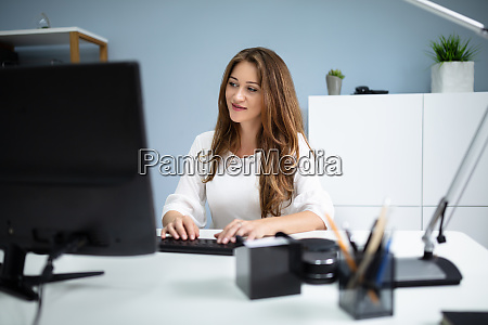 smiling businesswoman typing on computer keyboard