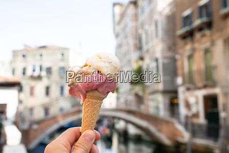 persons hand holding ice cream cone
