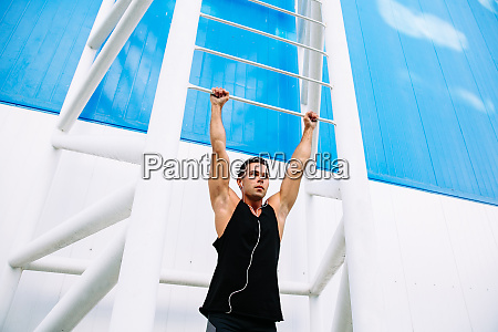 muscular man doing pull ups outdoors