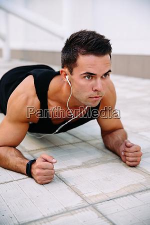 sportsman doing push ups on elbows
