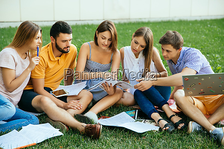 group of studying students sitting on