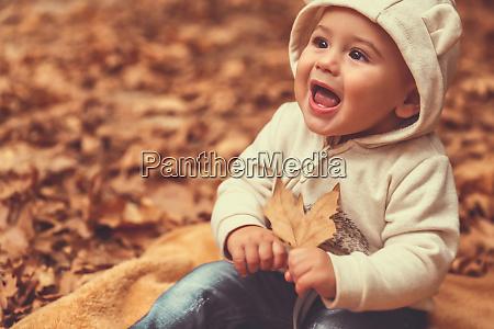 happy boy in autumn forest