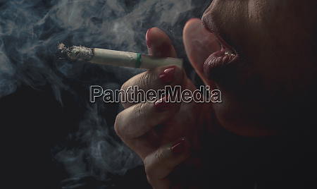 woman with red nail is smoking