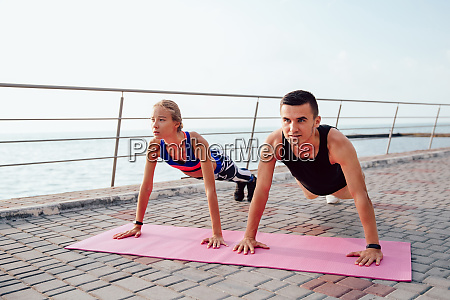 young sportswoman and sportsman doing plank