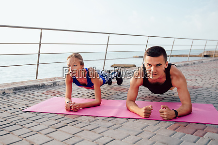 concentrated sportswoman and sportsman doing plank